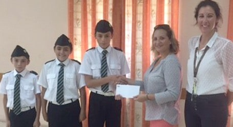 Amy Talbot, Director of Talbot & Bons, presenting the cheque for €1,300.00 to Giulio Aquilina, a member of the Salesian Brigade, who is currently learning to play the Fife. Looking on are two 'A Company' members Sion and Deemer Aquilina and entertainment.com.mt Events Manager Stephanie Camilleri
