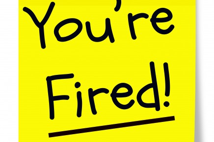 A yellow sticky memo pad note with black writing that says You're Fired!